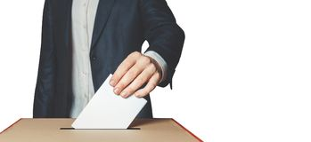 Man Voter Putting Ballot Into Voting box. Democracy Freedom Concept Isolated With Copy-Space. Unrecognizable male voter holds in his hand a ballot above the Stock Photos