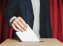 Man Voter Putting Ballot Into Voting box. Democracy Freedom Concept On Red Background. Unrecognizable male voter holds in his hand a ballot above the ballot box Stock Photography