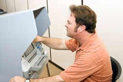 Man Votes on Touch Screen. Man casting his ballot on a touch screen voting machine Royalty Free Stock Photo