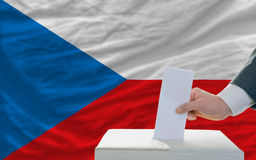 Man voting on elections in czech. Man putting ballot in a box during elections in czech in fornt of flag Royalty Free Stock Image