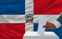 Man voting on elections in dominican republi. Man putting ballot in a box during elections in dominican republic in fornt of flag Stock Images