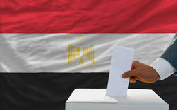 Man voting on elections in egypt. Man putting ballot in a box during elections in egypt in fornt of flag Stock Image