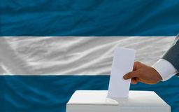 Man voting on elections in el salvador. Man putting ballot in a box during elections in el salvador in fornt of flag Royalty Free Stock Photo