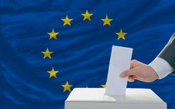 Man voting on elections in europe. Man putting ballot in a box during elections in europe in fornt of flag Royalty Free Stock Images