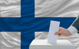 Man voting on elections in finland. Man putting ballot in a box during elections in finland in fornt of flag Stock Image