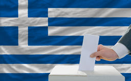 Man voting on elections in greece. Man putting ballot in a box during elections in greece in fornt of flag Royalty Free Stock Photos