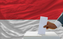 Man voting on elections in indonesia. Man putting ballot in a box during elections in indonesia in fornt of flag Royalty Free Stock Photo