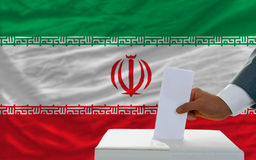 Man voting on elections in iran. Man putting ballot in a box during elections in iran in fornt of flag Stock Photography