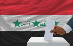 Man voting on elections in iraq. Man putting ballot in a box during elections in iraq in fornt of flag Royalty Free Stock Image