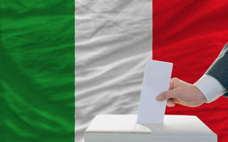 Man voting on elections in italy in front of flag. Man putting ballot in a box during elections in italy in fornt of flag Royalty Free Stock Image