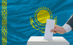 Man voting on elections in kazakhstan. Man putting ballot in a box during elections in kazakhstan in fornt of flag Stock Photography