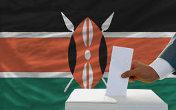 Man voting on elections in kenya. Man putting ballot in a box during elections in kenya in fornt of flag Royalty Free Stock Image