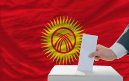 Man voting on elections in kyrghyzstan. Man putting ballot in a box during elections in kyrghyzstan in fornt of flag Royalty Free Stock Images