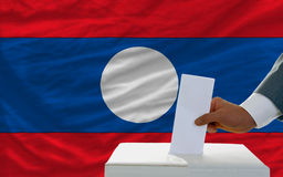 Man voting on elections in laos in front of flag. Man putting ballot in a box during elections in laos in fornt of flag Royalty Free Stock Photos