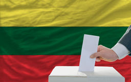 Man voting on elections in lithuania. Man putting ballot in a box during elections in lithuania in front of flag Stock Photo