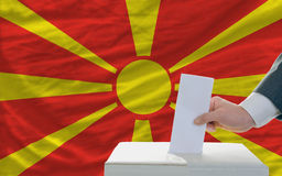 Man voting on elections in macedonia. Man putting ballot in a box during elections in macedonia in front of flag Stock Images
