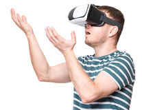 Man in VR glasses. Amazed handsome man wearing virtual reality goggles watching movies or playing video games gesticulating hands. Surprised male looking in VR Royalty Free Stock Photo