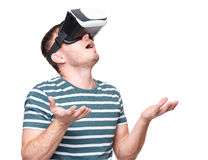 Man in VR glasses. Amazed handsome man wearing virtual reality goggles watching movies or playing video games gesticulating hands. Surprised male looking in VR Royalty Free Stock Image