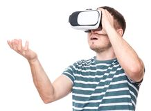 Man with VR glasses. Amazed man wearing virtual reality goggles watching movies or playing video games gesticulating hands, isolated on white background Royalty Free Stock Photography