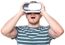 Man with VR glasses. Amazed man wearing virtual reality goggles watching movies or playing video games gesticulating hands, isolated on white background Royalty Free Stock Image