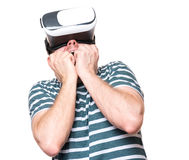 Man in VR glasses. Amazed man wearing virtual reality goggles watching movies, isolated on white background. Surprised male worried and scared making face Stock Image