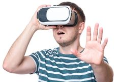 Man with VR glasses. Amazed man wearing virtual reality goggles watching movies or playing video games gesticulating hands, isolated on white background Royalty Free Stock Photos