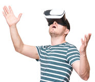 Man in VR glasses. Amazed man wearing virtual reality goggles watching movies or playing video games gesticulating hands, isolated on white background. Surprised Royalty Free Stock Image