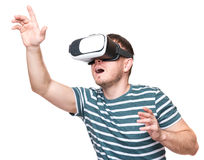 Man in VR glasses. Amazed man wearing virtual reality goggles watching movies or playing video games gesticulating hands, isolated on white background. Surprised Royalty Free Stock Images