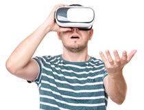 Man in VR glasses. Amazed man wearing virtual reality goggles watching movies or playing video games gesticulating hands, isolated on white background. Surprised Royalty Free Stock Photography