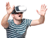 Man in VR glasses. Amazed man wearing virtual reality goggles watching movies or playing video games gesticulating hands, isolated on white background. Surprised Stock Images