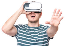 Man in VR glasses. Amazed man wearing virtual reality goggles watching movies or playing video games, isolated on white background. Surprised male looking in VR Stock Photography