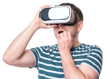 Man in VR glasses. Amazed man wearing virtual reality goggles watching movies or playing video games, isolated on white background. Surprised male worried and Stock Image