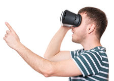 Man in VR glasses. Amazed man wearing virtual reality goggles watching movies or playing video games, isolated on white background. Surprised male in VR glasses Stock Photo