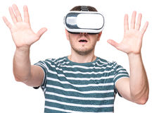 Man in VR glasses. Amazed man wearing virtual reality goggles watching movies or playing video games, isolated on white background. Surprised male in VR glasses Royalty Free Stock Photography