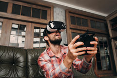Man in vr glasses controlling something invisible. Young male playing video games with virtual reality headset and joystick or driving with remote control Royalty Free Stock Photography