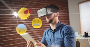 Man with VR glasses and digital tablet using emojis Royalty Free Stock Image