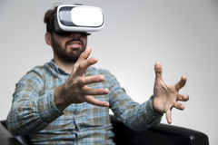 Man in vr glasses gesturing. Portrait of a bearded man in a leather armchair and playing a virtual reality game. He is sitting with his hands grabbing the air royalty free stock images