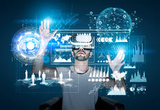 Man in vr glasses and glowing graphs Royalty Free Stock Photos