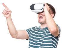 Man in VR glasses. Happy man wearing virtual reality goggles watching movies or playing video games - closeup. Cheerful laughing male looking in VR glasses Stock Image
