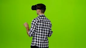 Man in vr glasses on head. Back view. Green screen