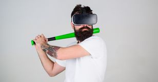 Man in VR glasses with hipster beard and tattoo posing with baseball bat isolated on gray background. Amateur player. Training batting skills in simulation game stock images