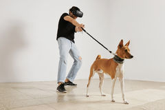 Man VR glasses holding a dog's leash royalty free stock images