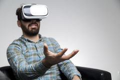 Man in vr glasses holding invisible item. Portait of a bearded man in a leather armchair and playing a virtual reality game. He is sitting with his hand holding stock images