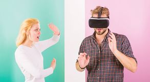 Man VR glasses involved video game while girl try to wake him up. Video game captured imagination of guy. Wife tries to. Help him back into real life. Video royalty free stock photography