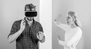 Man VR glasses involved video game while girl try to wake him up. Video game captured imagination of guy. Wife tries to. Help him back into real life. Video royalty free stock photo