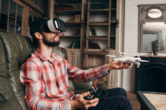 Man in vr glasses launching drone indoors. Young male controls quadrocopter using virtual reality headset and remote control Royalty Free Stock Photo