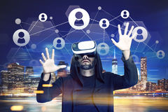 Man in VR glasses, network in a night city Stock Photos