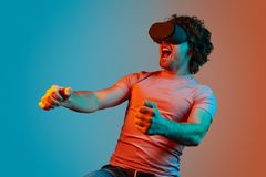 Man in VR glasses playing racing game stock image