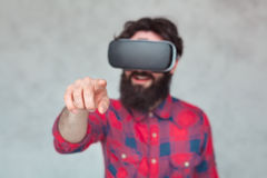 Man in VR glasses pointing at camera. Young male wearing VR glasses and pointing at camera on grey concrete wall Stock Photos
