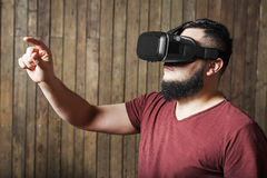Man with vr glasses showing gesture. Virtual reality glasses. Bearded guy with virtual reality glasses standing over wooden background. concept of nosy stock photo